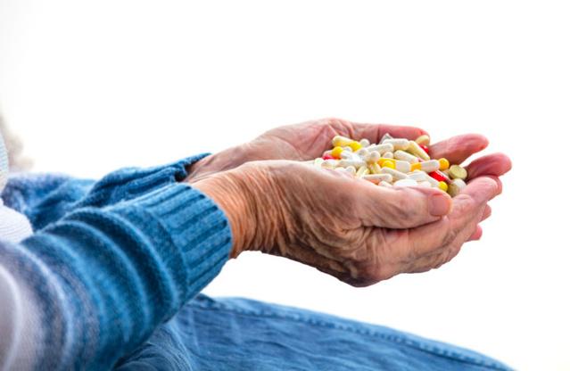 Femme Senior tenant des antibiotiques dans ses mains