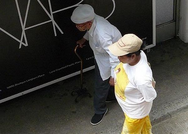 Une Philippine aidant un vieux hongkongais